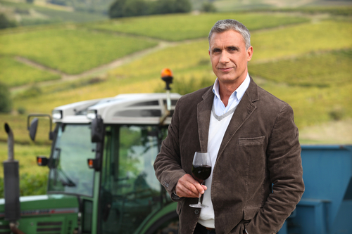Vineyard owner stood in field with glass of wine